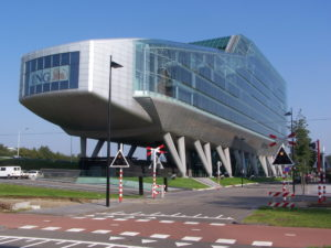 Picture of a beautiful glass ING Bank in Amsterdam on stilts, by a railroad track.