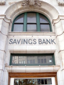 "Picture of the phrase ""Savings Bank"" placed high on a stone bank facade."